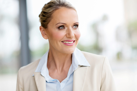 mid age: attractive mid age businesswoman looking outside window