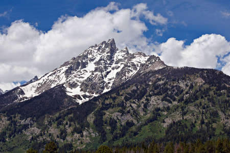 A crown of clouds seems to adorn this jagged glacier covered mountain peak at Grand Teton National Park    Grand Teton National Park lies in Northwestern Wyoming about ten miles south of Yellowstone National Park  Stock Photo