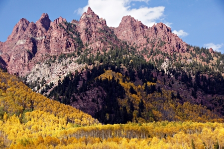 At Maroon Lake Colorado jagged spires form the backdrop to peak golden autumn aspen trees