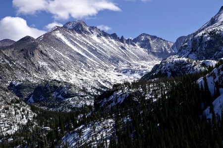 colorado rocky mountains: This is Longs Peak in Rocky Mountain National Park as seen from the trail between Bear and Dream Lakes     Here Longs Peak rises against a partly cloudy blue sky and dominates a high valley on its western slope