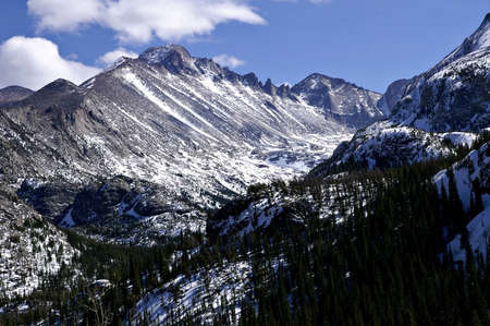 longs peak: This is Longs Peak in Rocky Mountain National Park as seen from the trail between Bear and Dream Lakes     Here Longs Peak rises against a partly cloudy blue sky and dominates a high valley on its western slope