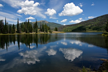 In this scene, afternoon clouds reflect from Pearl Lake s deep blue waters    Steamboat and Pearl Lakes State Parks are located in Clark County near the north west quadrant of Colorado just south of Wyoming  photo