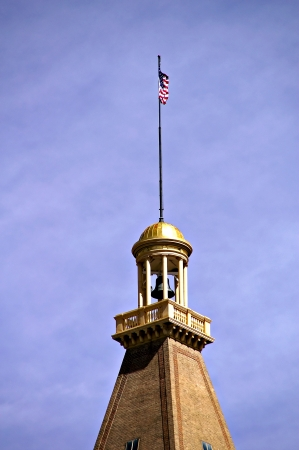 Denver, Colorado, USA - April 17, 2011 - A bell tower and flag sit atop a Downtown Denver building on a spring day.