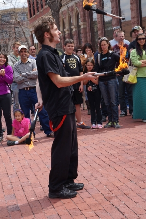 BOULDER, COLORADO USA - MAY 04, 2013 - This street performer fearlessly juggles three wands of fire before an entranced crowd in Boulder Colorado Editorial