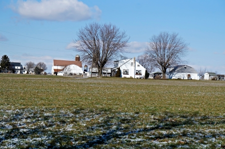 Lancaster, PA, USA - Feb 09, 2013 - This row of farm houses can be seen across an open field on a sunny winter afternoon in Lancaster Pennsylvania.