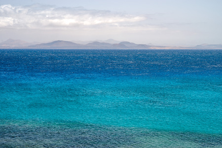 Atlantic ocean with rock formations of  Fuerteventura in horizon