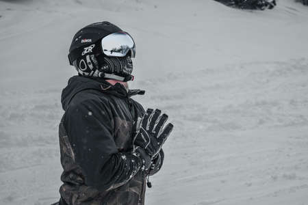 A guy in a ski helmet and mask holds his hands together looking into the distance. Kneeling. Around the snow. Through the glasses you can see the surrounding landscape Éditoriale