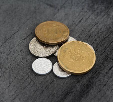 Close up of Stable of Netherlands Antillean guilder coins on black background