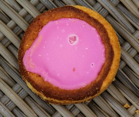 close up of Self made Dutch Butter Cake (Boterkoek) cookie with pink glaze, fresh baked from the oven. Displayed on wooden background. Made in the kitchen