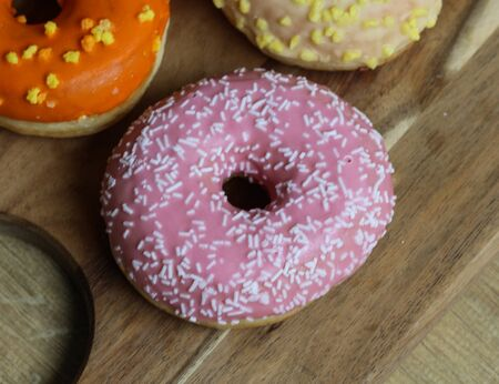 close up of a single strawberry donut with sprinkles on a wooden background