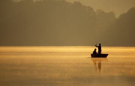 釣り人のペアは、湖畔に美しい、黄金、霧の深い朝釣りを楽しみます。 写真素材