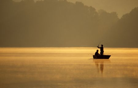 outdoorsman: A pair of anglers enjoy a beautiful, golden, misty morning fishing on a lake.