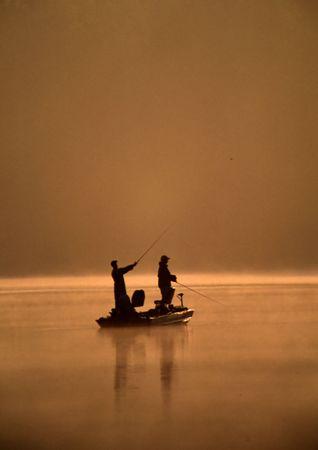 釣り人のペアは霧の湖でボートを使った釣り.