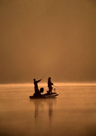 A pair of anglers are fishing from a boat on a misty lake.