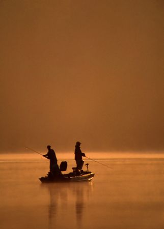 outdoorsman: A pair of anglers fishing as one angler sets the hook on a fish. Stock Photo