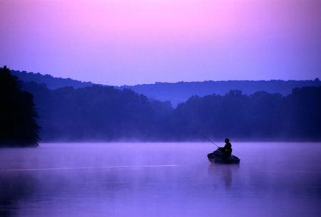 釣り人は低音のための湖の釣りに静かな朝を費やしています。