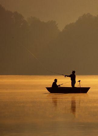 釣り人のペア、美しい黄金の朝に釣りをしています。 写真素材