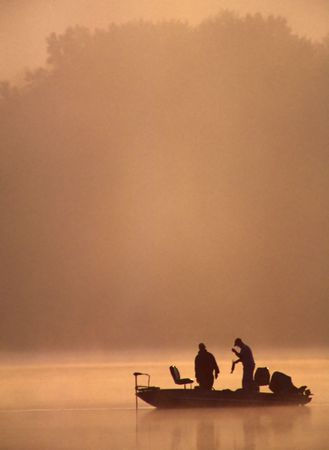 A couple of fishermen are admiring the Large Mouth Bass they just caught on a beautiful misty morning. Stock Photo