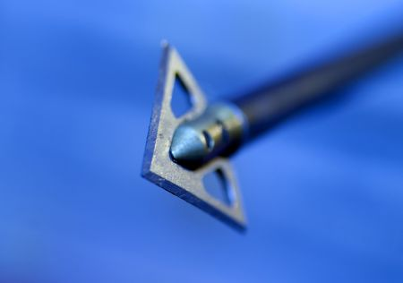 aiming: Shallow depth of field image of an arrow flying in the direction of the viewer. Stock Photo