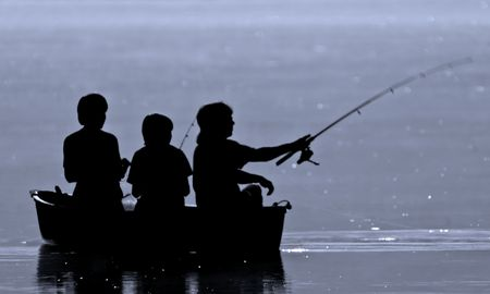 Three boys fishing from a boat in silhouette. Stock Photo