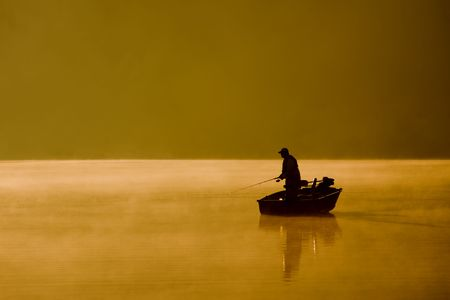 rowboat: A single angler enjoys fishing from a boat on a beautiful morning. Stock Photo