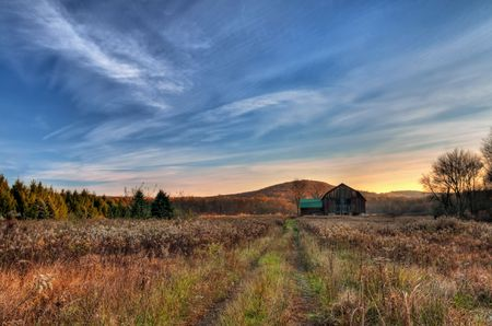 Morning arrives at a rural farm with rustic barn. photo