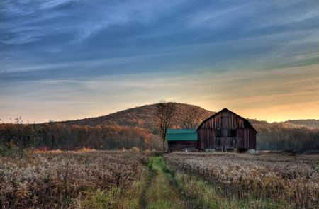 Sun begins to rise over a rustic old barn.