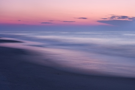 A beautiful pastel colored sunset on a quiet, secluded beach.