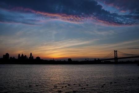 Philadelphia skyline in silhouette against a colorful sunset. Stock Photo