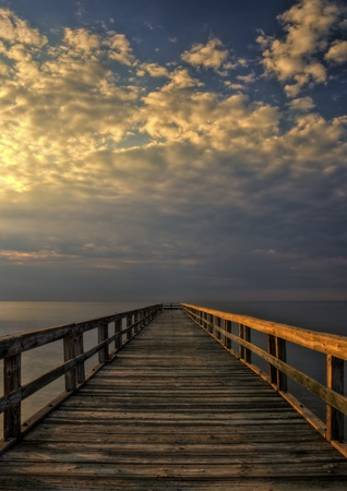 Long wooden fishing pier at Port Mahon, Delaware extending over the Delaware Bay. Stock Photo