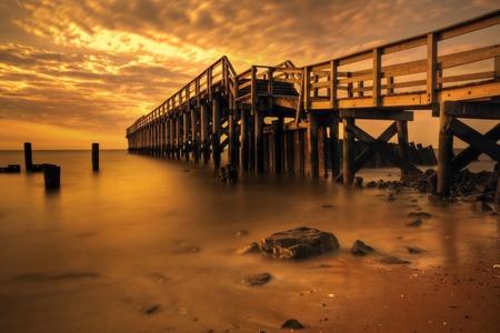 Delaware Bay Fishing Pier illuminated by golden morning light.