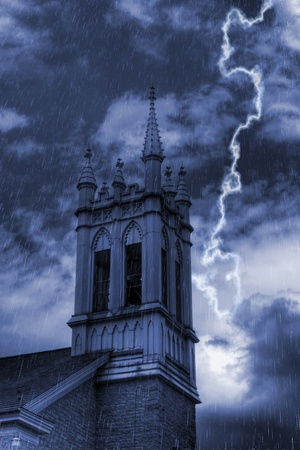 Rain and lightning on a stormy night over the church bell tower. Stock Photo