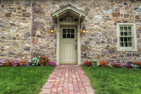 home front: Path and door entrance of a stone home with spring flowers and lush lawn.
