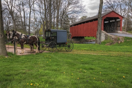 pennsylvania: Amish horses and buggy parked near a covered bridge in Lancaster County, Pennsylvania. Stock Photo