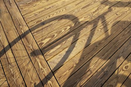 Shadow cast by bicyclist on the boardwalk