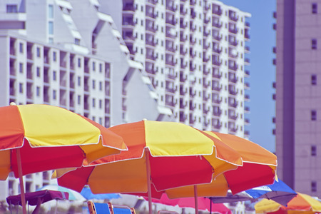 Colorful beach umbrellas with hotels in background  Stok Fotoğraf