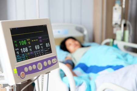 sign: Vital sign monitor with background of blurry Asian woman patient