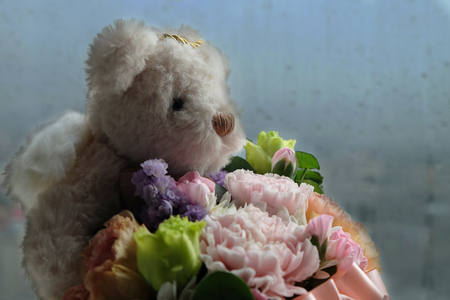 Bear angel doll holding flowers with background of blurry raindrops on the glass window in raining season