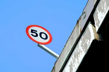 Round speed limit sign at 50 on highway Stock Photo