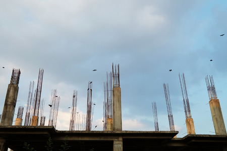 Under constructional house with unfinished steel stakes