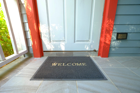 Welcome doormat in front of the wooden door nearby a green garden