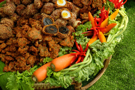 Hard boiled chicken eggs and century eggs covered by fried fish patty on the rattan tray decorated by carrots, chili and green lettuce vegetables Stock Photo