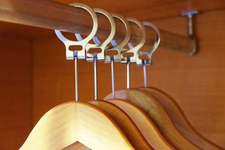 Closeup of hangers without clothes  in the wooden closet