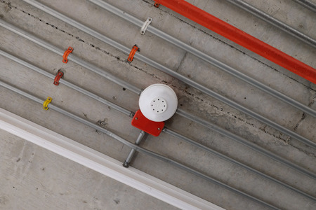 White smoke detector installed on the ceiling at car parking area with pipeline of electrical wiring Archivio Fotografico - 97128106