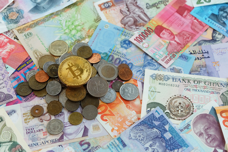 Gold bitcoin coin on top over international traditional coins and banknotes