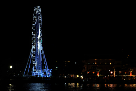 Giant Ferris wheel decorated by blue and white light at the riverbank at night with copy space