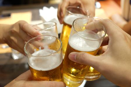 Persone che celebrano tostando la birra nel bicchiere Archivio Fotografico