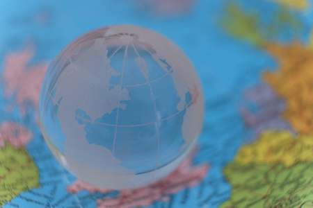 Transparent glass terrestrial globe model on the blurry international paper map
