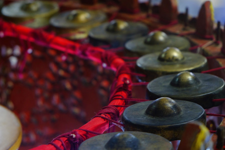 Closeup of old brass ancient Asian musical instruments in semicircle around the position of musician Foto de archivo