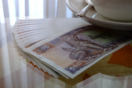 Closeup of cup of coffee over the Myanmar currency banknotes on glass table